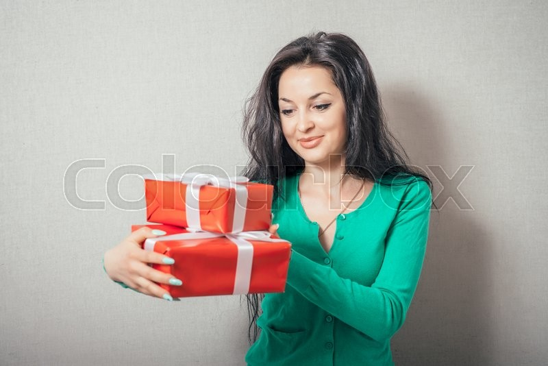 Portrait of casual young happy smiling woman hold red gift box. Isolated studio background female model, stock photo