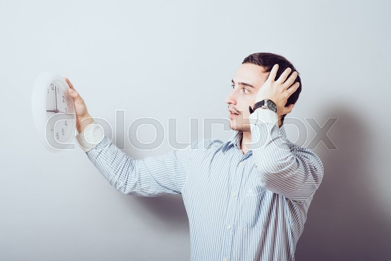 Stock image of 'A man looking at the big clock. Gray background'