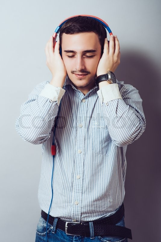 Stock image of 'Cheerful guy enjoying loud music holding them tightly to ears'