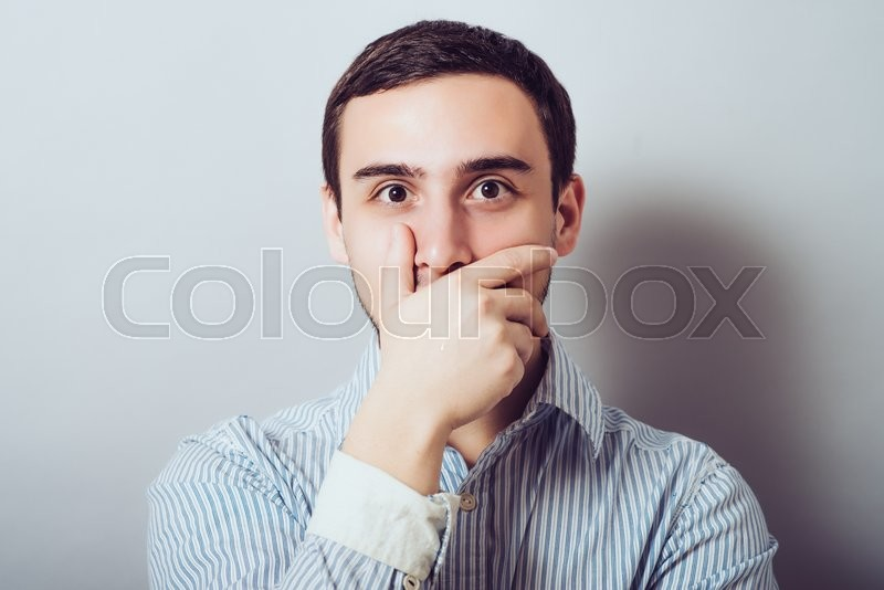 Young handsome man covered her mouth in surprise. Gesture. On a gray background, stock photo