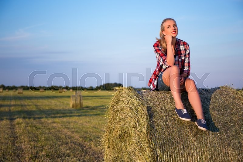Stock image of 'country concept - young beautiful woman sitting on haystack in field'