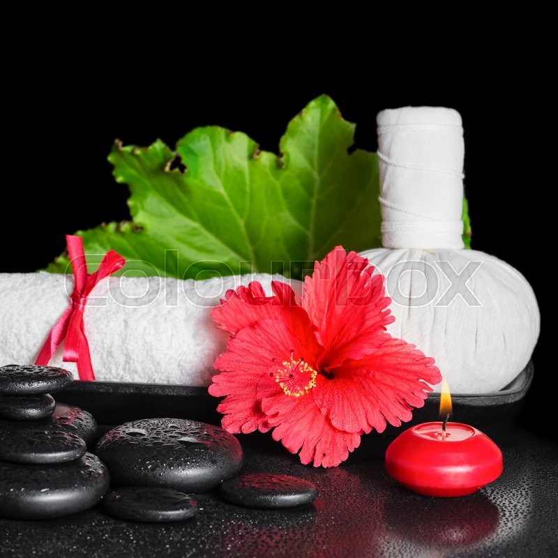 Stock image of 'Spa still life of red hibiscus flower with dew, candles, leaf, thai herbal compress ball and rolled towel on zen stones, closeup'