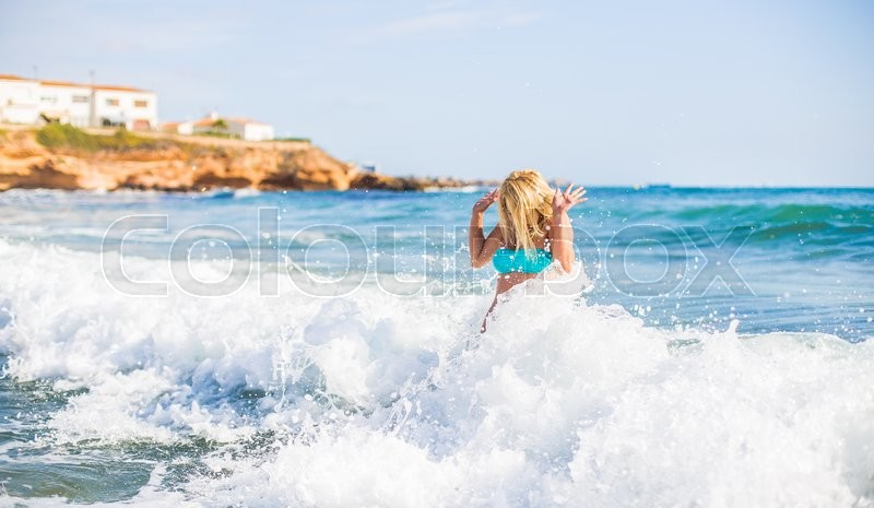 Stock image of 'beautiful young blonde woman jumping in big waves in the blue sea bright day in the resort in Europe'