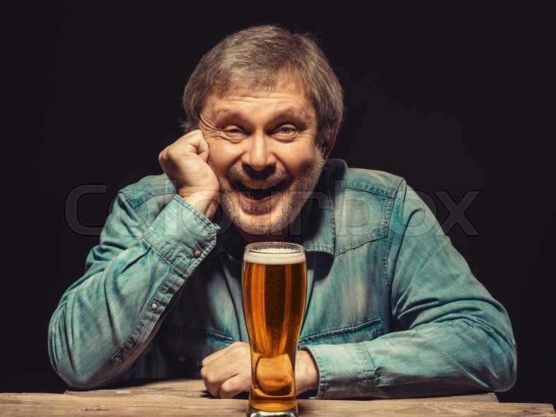 Stock image of 'Enjoying his favorite beer.  The front view of handsome smiling  man as fan in denim shirt with glass of beer, sitting at the wooden table'