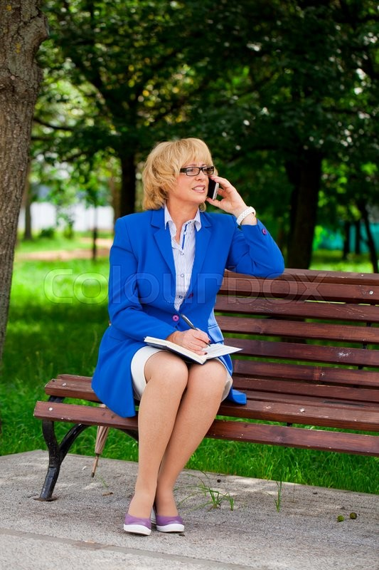 Stock image of 'Elderly business woman in jacket sittin on bench with daily log, outdoor summer park'
