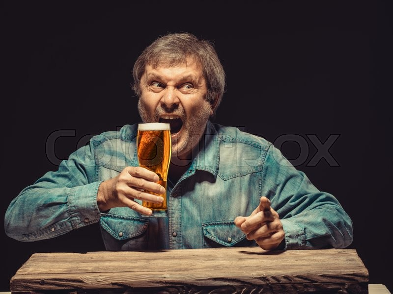 Stock image of 'The front view of handsome screaming man as fan in denim shirt with glass of beer, sitting at the wooden table. Concept of emotional fan, interested showing something'