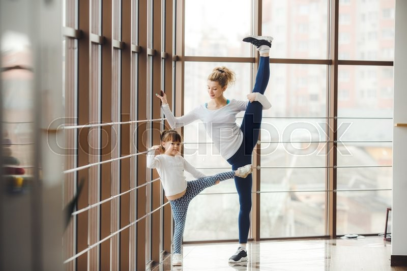 Stock image of 'Mother learning daughter to make a high leg strech'