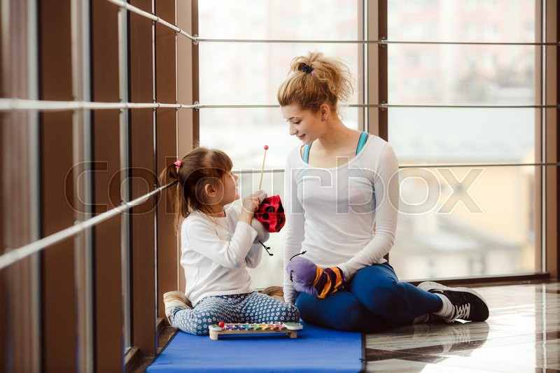 Stock image of 'Mother and daughter makeing yoga in the gym'