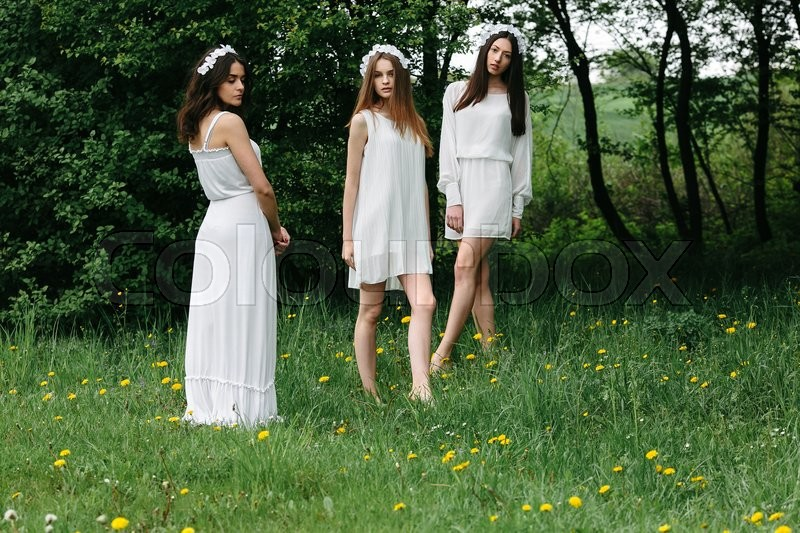 Stock image of 'three beautiful girls posing in the garden at the camera'