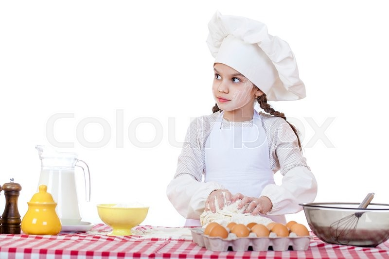 Stock image of 'Portrait of a little girl in a white apron and chefs hat knead the dough in the kitchen, isolated on a white background'