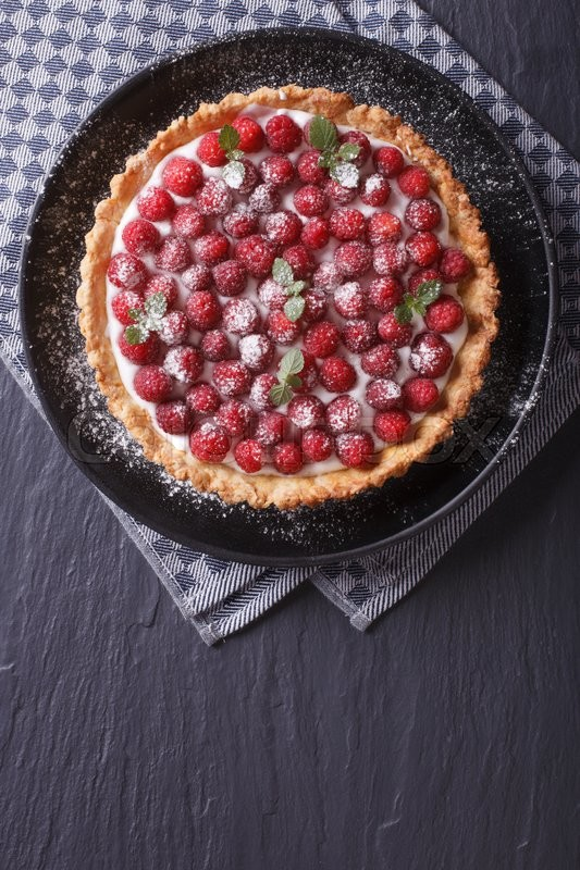 Stock image of 'Delicious raspberry tart with whipped cream on a plate vertical view from above\'