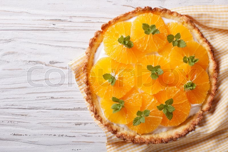 Stock image of 'Tasty orange citrus tart with white cream and mint on the table. horizontal view from above\'