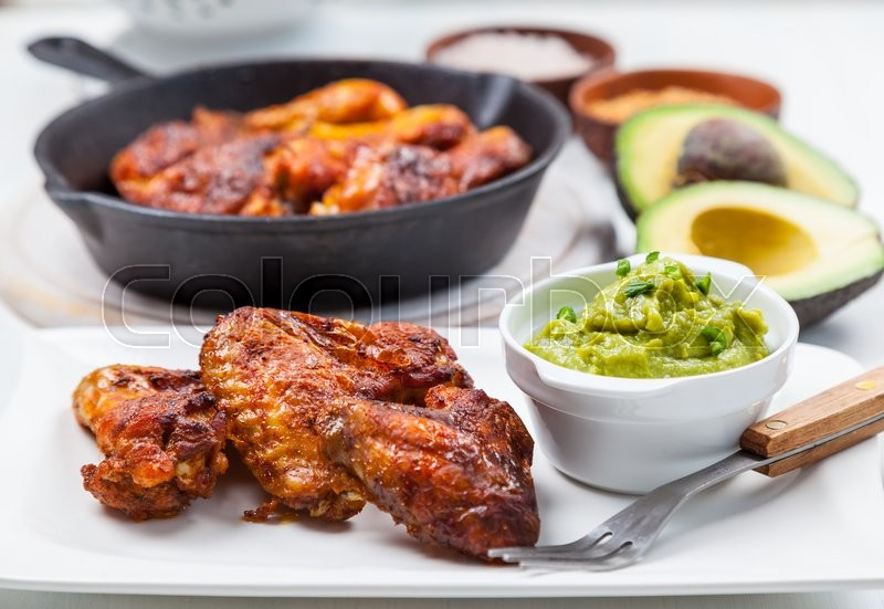 Stock image of 'Grilled chicken legs and wings with guacamole, frish salad and spicies'