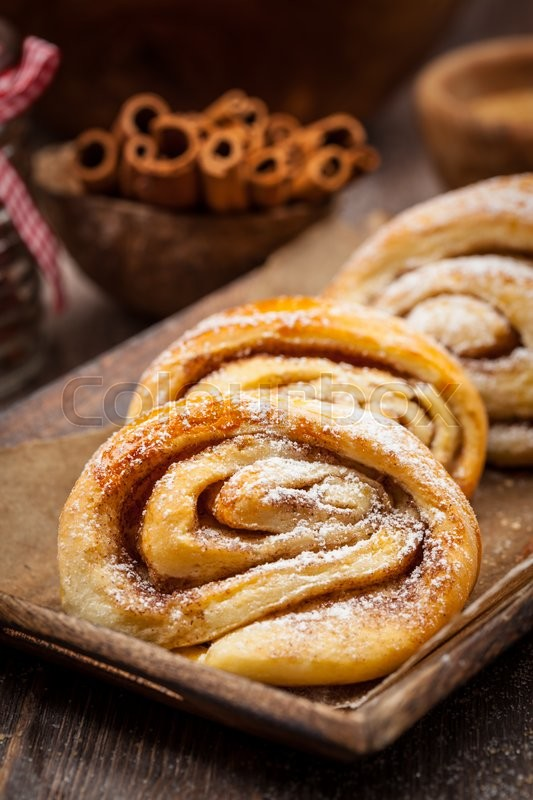 Stock image of 'Homemade cinnamon rolls on wooden table'
