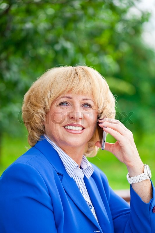 Stock image of 'Close up portrait of an elderly beautiful blonde woman talking on a cell phone in a summer park'