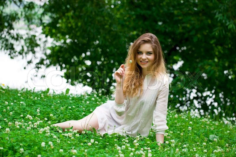 Stock image of 'Sexy young blonde woman in white dress sitting on green grass in summer park'