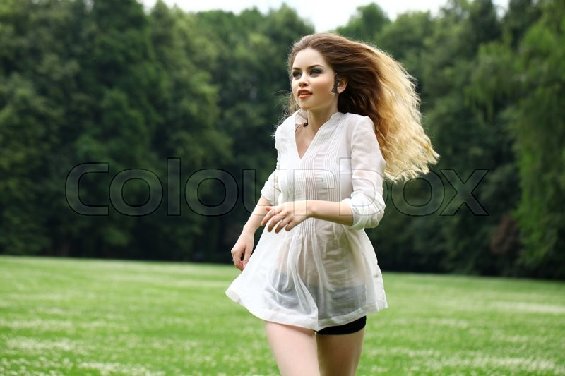 Stock image of 'Young beautiful girl in the white shirt is running on the green field in summer park'
