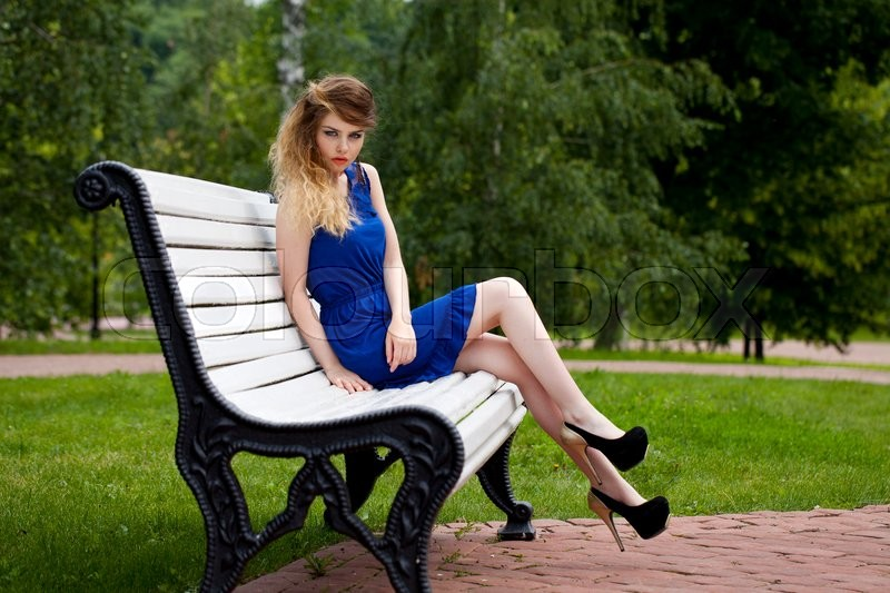 Stock image of 'Young beautiful blonde girl in blue dress sitting on a bench in summer park'