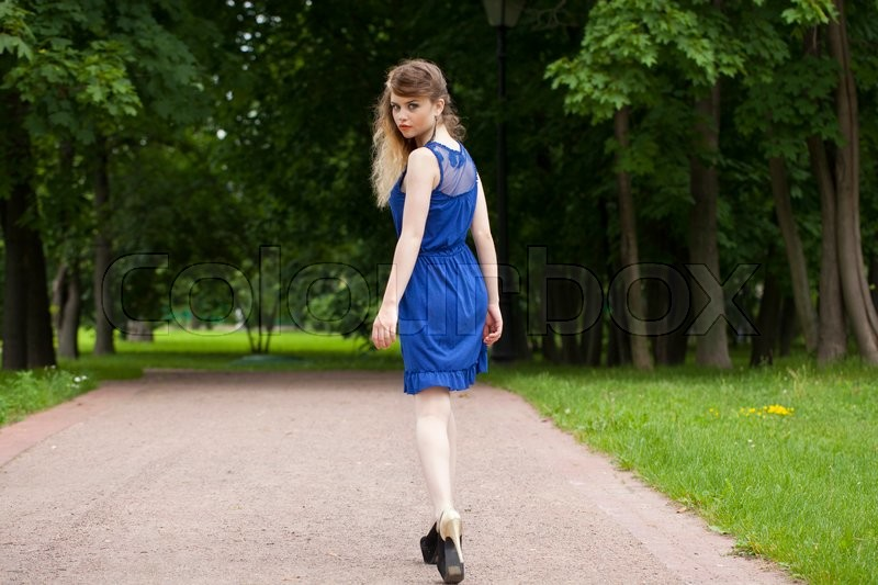 Stock image of 'Portrait in full growth, attractive young blonde woman in blue dress walking in summer park'