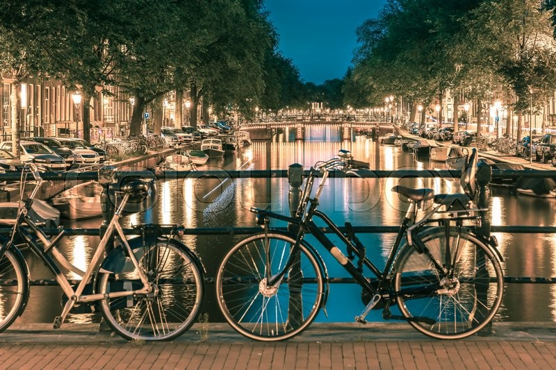 Stock image of 'Night  illumination of Amsterdam canal and bridge with typical dutch houses, boats and bicycles, Holland, Netherlands.. Toning in cool tones'