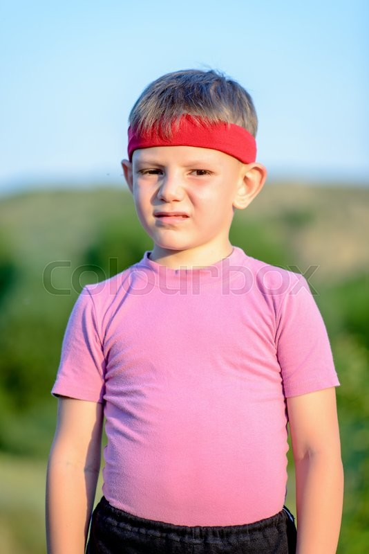 Stock image of 'Half Body Shot of a Cute White Young Boy with Red Warrior Headband, Smiling at the Camera Against Blurry Field.'