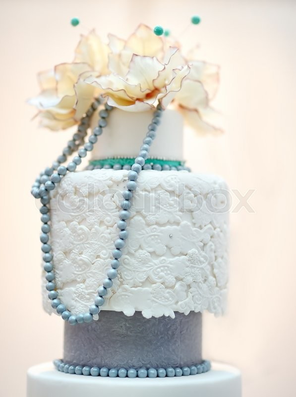 Stock image of 'Delicious white and grey wedding cake decorated with flowers'