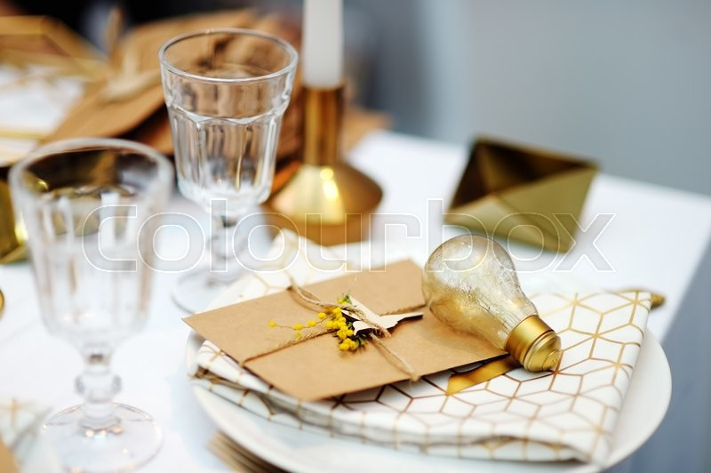 Stock image of 'Stylish gold table set with letter'