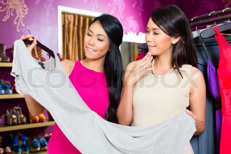 Stock image of 'Asian young sales lady offering gown to woman in fashion store'