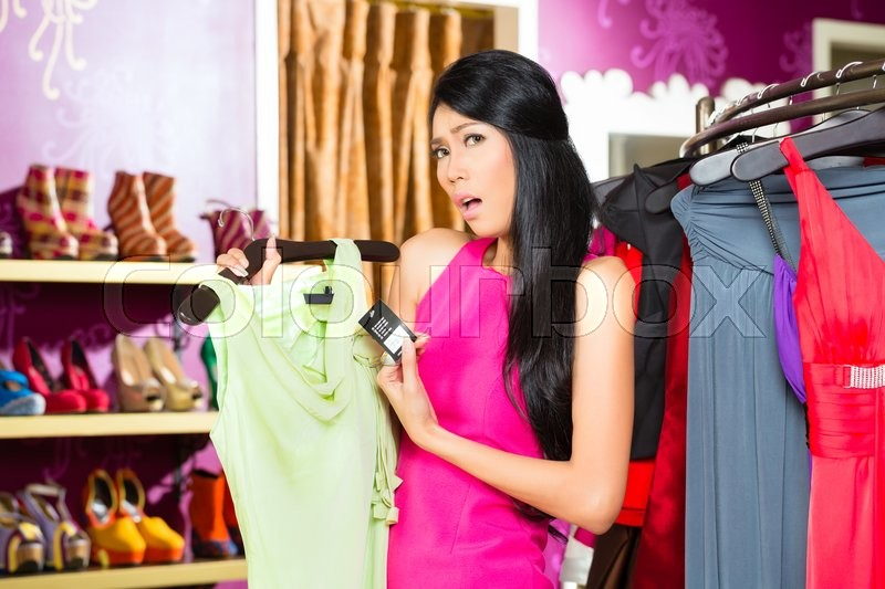 Stock image of 'Asian young woman choosing dress in fashion store'