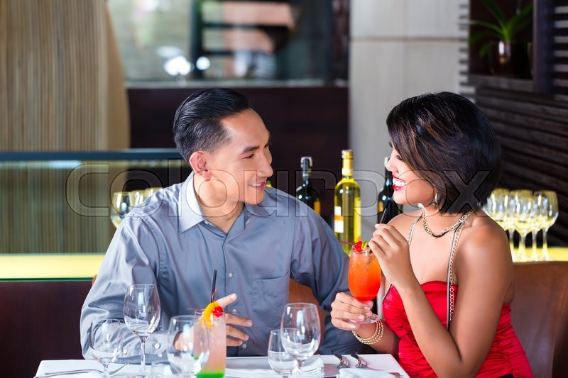 Stock image of 'Asian couple drinking cocktails in fancy bar'
