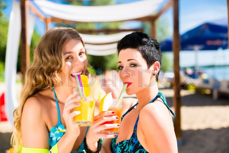 Stock image of 'Two women in beach bar drinking cocktails'