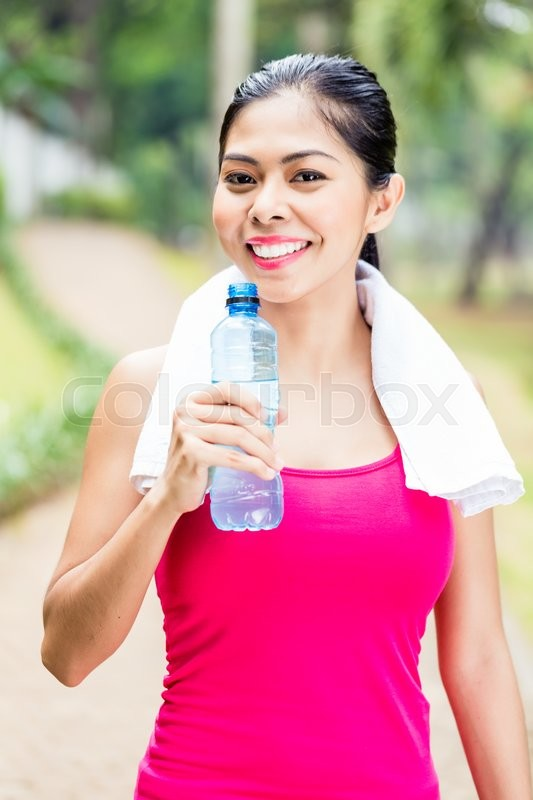 Stock image of 'Asian woman having successful sport training giving thumbs up with water bottle in her hands'