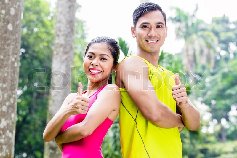 Stock image of 'Asian woman and man during jogging training standing shoulder to shoulder looking in tropical park'