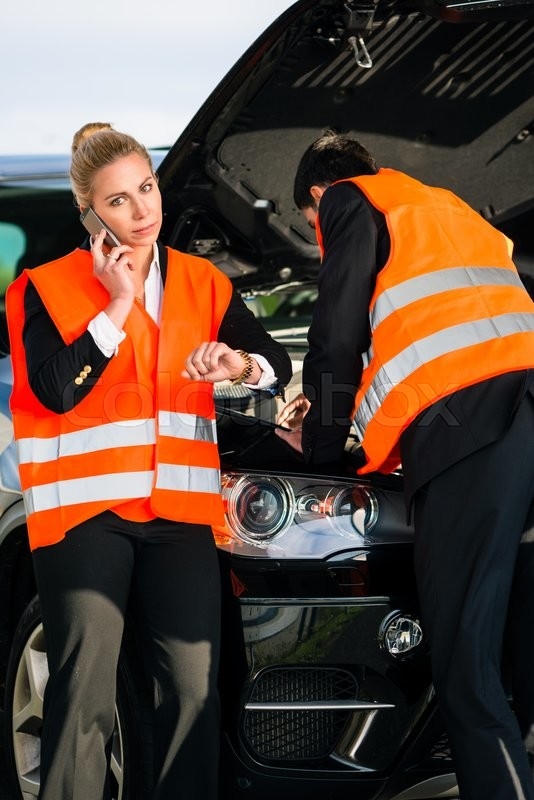 Stock image of 'Couple with car breakdown wearing reflective vests calling towing company'