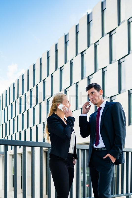 Stock image of 'Business people working outdoors in city on bridge in front of office building'