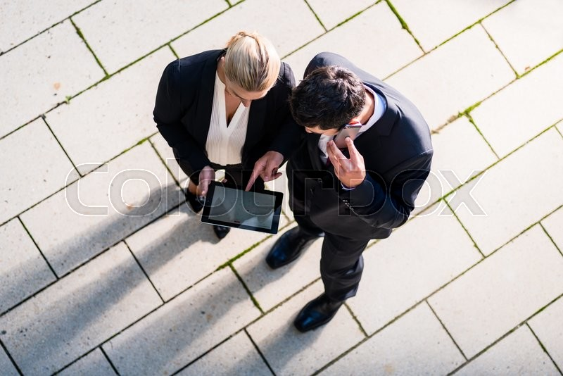 Stock image of 'Business man and woman  with tablet computer standing on square, seen in top view'