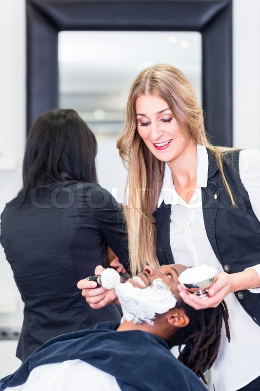 Stock image of 'Barber soaping customer getting ready to shave him'