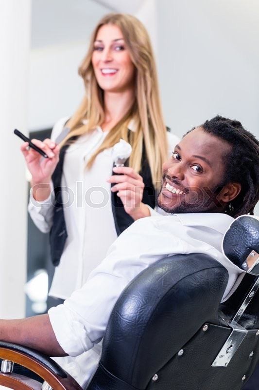Stock image of 'Happy barber and smiling customer in salon'