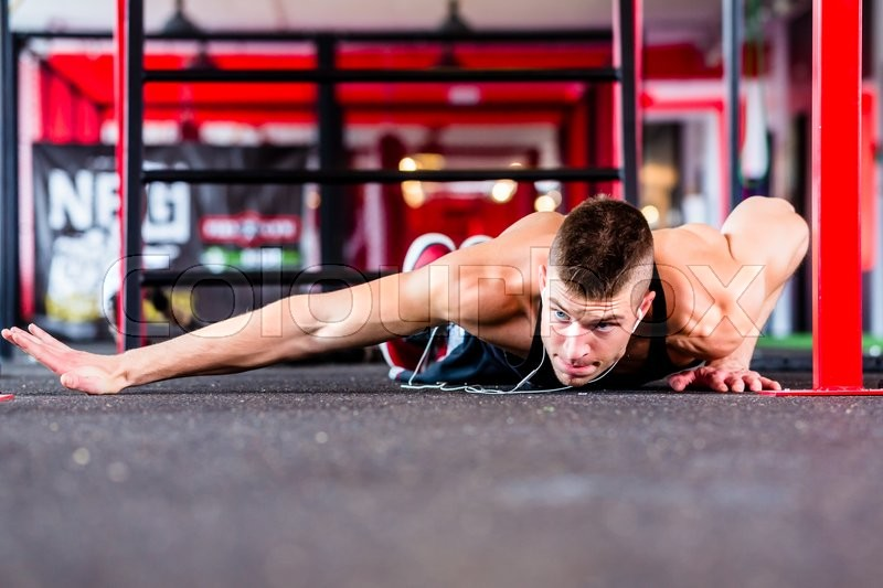 Stock image of 'Man exercising doing push-up on floor of sport fitness gym'