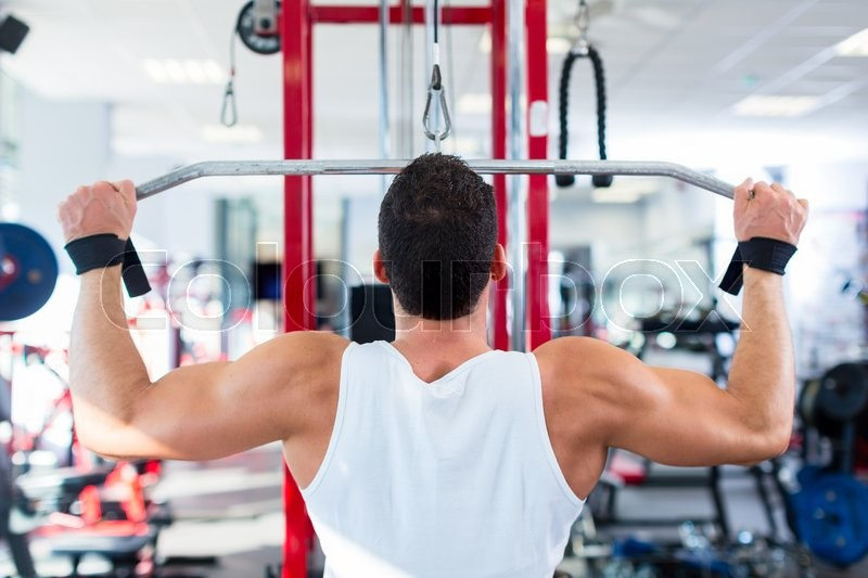 Stock image of 'Man doing bodybuilding sport by exercising lifting dumbbells in fitness club or gym'