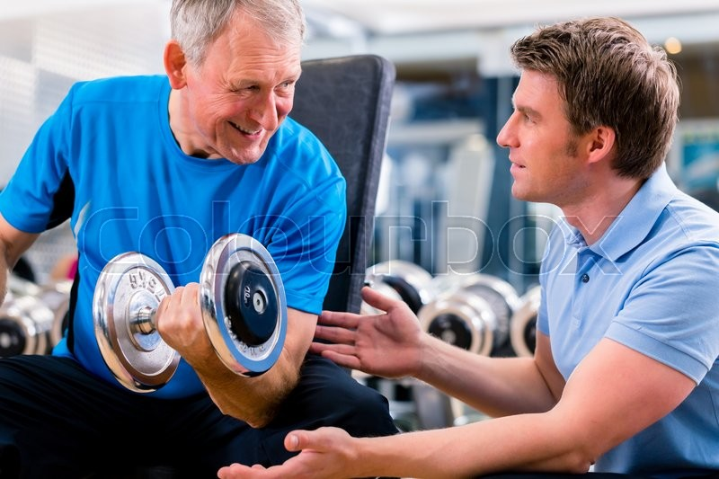 Stock image of 'Senior man and trainer at exercise in gym with dumbbell weights'