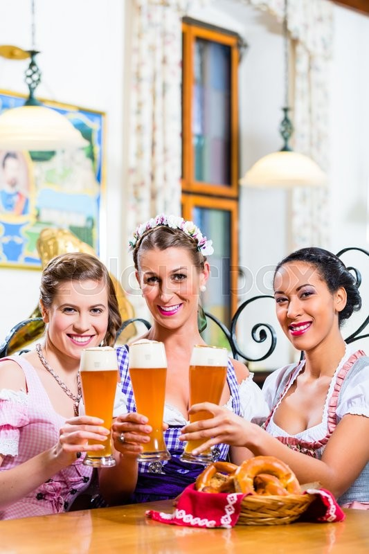 Stock image of 'Group of people with wheat beer in Bavarian pub clinking glasses'