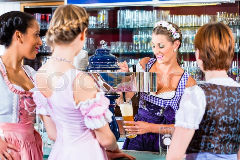 Stock image of 'Innkeeper in Bavarian pub with customers'