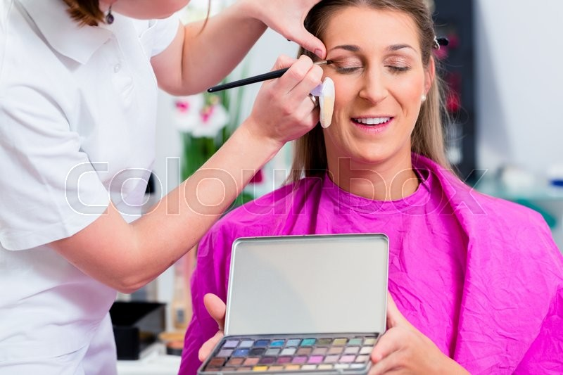 Stock image of 'Woman with beautician in cosmetic salon receiving makeup'