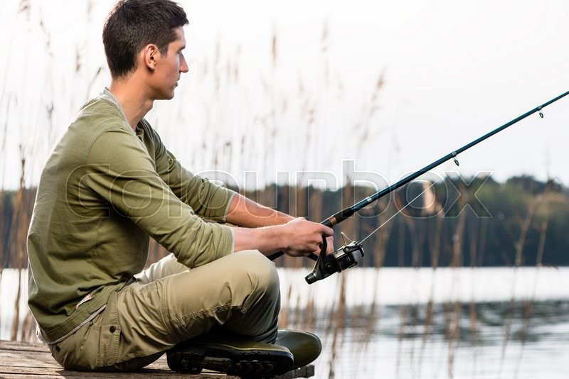 Stock image of 'Man relaxing fishing or angling at lake sitting cross-legged on jetty'