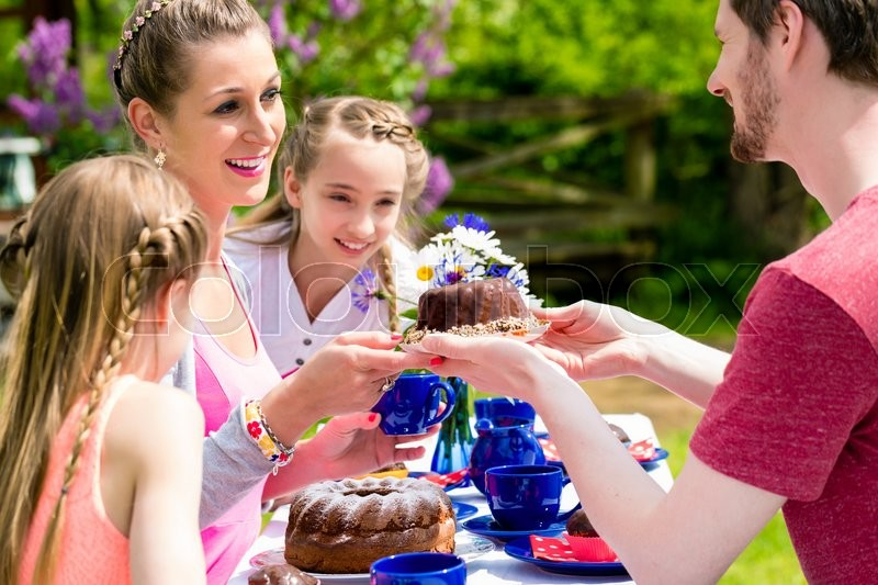 Stock image of 'Family having coffee time in garden eating cake'