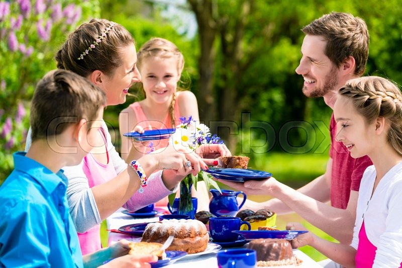 Stock image of 'Family having coffee and cake in garden in front of their home at a table outdoors'
