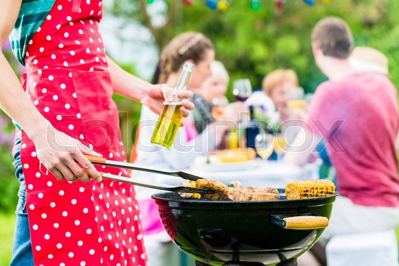 Stock image of 'Yong man at the bbq grill turning the meat, in the background friends are having garden party'