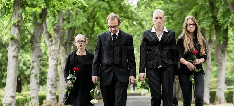 Stock image of 'Family on cemetery walking down alley at graveyard with roses'