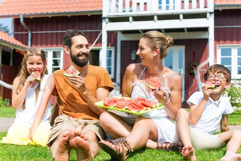 Stock image of 'Family sitting in grass in front of house eating water melon to refresh in summer'
